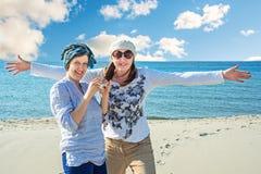 两名由海的快乐的妇女步行 免版税图库摄影