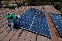 两名男性太阳工作者安装太阳电池板 免版税库存照片