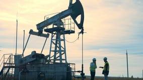 两名男性工作者的讨论过程在井架,抽油装置,油泵附近的 运转的油泵,在背景的抽油装置 股票视频