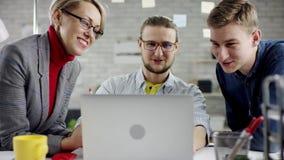 两名男性雇员站立在日间坐在计算机在现代明亮的设计事务所的女性雇员 股票视频