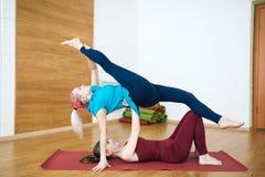 两名美丽的健身女孩杂技演员在健身房执行体操瑜伽锻炼 库存图片