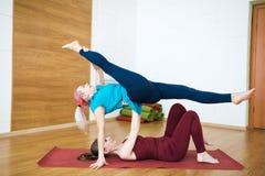 两名美丽的健身女孩杂技演员在健身房执行体操瑜伽锻炼 图库摄影