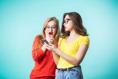 两名美丽的妇女使用一个智能手机 应用惊奇的女朋友,在屏幕上的消息 技术 免版税库存图片