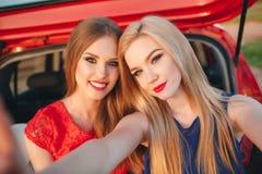 两名美丽的妇女在一辆红色汽车旅行 免版税图库摄影
