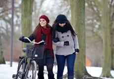 两名美丽的妇女在公园的一冷颤的天 免版税库存图片