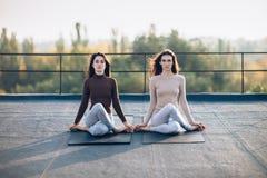 两名美丽的妇女执行在屋顶的冥想的姿势 图库摄影