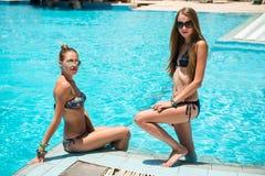 两名美丽的妇女松弛近的游泳池 免版税库存图片