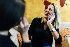 两名美丽的妇女谈话在咖啡馆的电话 免版税库存照片