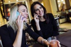 两名美丽的妇女谈话在咖啡馆的电话 库存图片