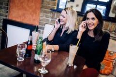 两名美丽的妇女谈话在咖啡馆的电话 免版税库存图片