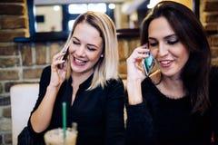 两名美丽的妇女谈话在咖啡馆的电话 库存照片
