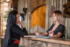 两名美丽的妇女谈话在招待会,有客户的管理员 免版税库存照片