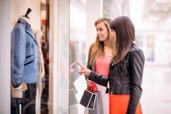 两名美好的妇女窗口购物 免版税库存照片