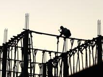 两名老挝建筑工人剪影  库存图片