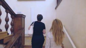 两名苗条妇女、攀登与栏杆的支的母亲和她的成人女儿木楼梯,户内 4k, 股票录像