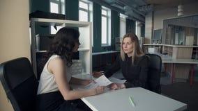两名苗条妇女坐在桌上在办公室并且谈话 股票视频