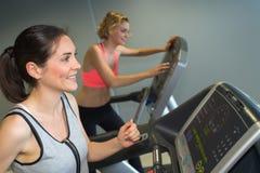 两名运动的妇女在机器在健身房中心跑 免版税库存图片