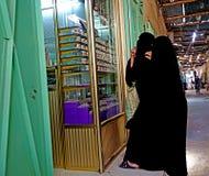 两名阿拉伯妇女在黑burqa穿戴了敬佩在市的souk的珠宝Rissani在摩洛哥 图库摄影