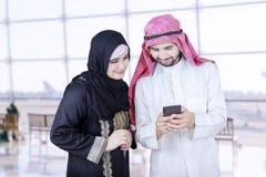 两名阿拉伯工作者用途手机在机场 免版税库存图片