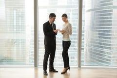 两名雇员谈话,使用数字式片剂,站立在大胜利 库存照片