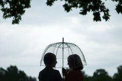 两名雨和谈话的妇女走的公园 友谊和人通信 多雨 免版税库存照片