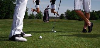 两名高尔夫球运动员和跳跃妇女 库存图片