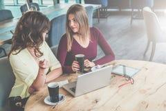 两名年轻可爱的妇女坐在咖啡馆,饮用的咖啡和谈话的圆的木桌上 企业生意人cmputer服务台膝上型计算机会议微笑的联系与使用妇女 图库摄影