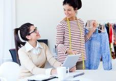 两名年轻女实业家与在她的数字式片剂一起使用offic 免版税库存照片