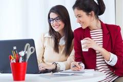 两名年轻女实业家与膝上型计算机一起使用在她的办公室 免版税库存图片