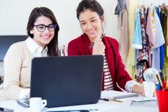两名年轻女实业家与膝上型计算机一起使用在她的办公室 库存图片