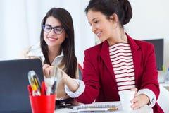 两名年轻女实业家与膝上型计算机一起使用在她的办公室 免版税库存照片