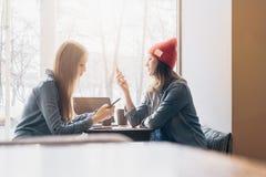 两名年轻女实业家侧视图坐在咖啡馆在桌上在窗口附近和使用智能手机的牛仔布衬衣的 免版税图库摄影