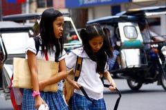 两名年轻学生聊天,当走在他们的途中到学校时 免版税图库摄影