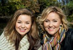 两名年轻微笑的妇女画象在秋天户外 库存照片