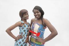 两名年轻微笑的妇女画象用在他们的臀部的手在从非洲,演播室射击的传统礼服 库存图片