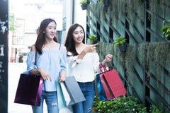 两名年轻愉快亚洲妇女购物室外 库存照片