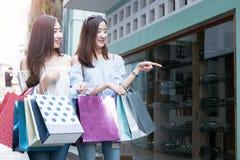 两名年轻愉快亚洲妇女购物室外 免版税图库摄影