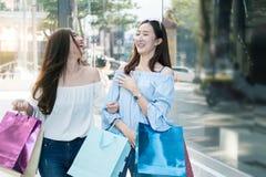 两名年轻愉快亚洲妇女购物室外 图库摄影