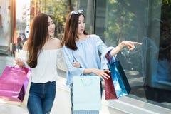 两名年轻愉快的亚裔妇女购物的室外商城 免版税库存图片