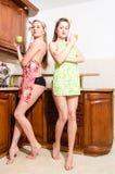 两名滑稽的美丽的年轻白肤金发&深色的画报妇女的图象围裙的在厨房里 库存照片
