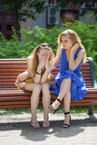 两名年轻美丽的妇女秘密在夏天绿化公园 图库摄影