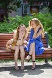两名年轻美丽的妇女秘密在夏天绿化公园 库存照片