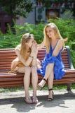 两名年轻美丽的妇女秘密在夏天绿化公园 免版税库存照片