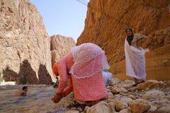 两名巴巴里人妇女在河的美好的颜色穿戴了在托德拉峡谷的河在摩洛哥 免版税库存照片