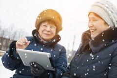 两名年长妇女设法推测板材 免版税库存照片