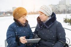 两名年长妇女设法推测板材 免版税库存图片