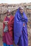 两名Maasai妇女站立靠近他们的房子神色在我的与想知道的照相机 免版税库存照片