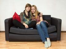两名yong妇女坐沙发 免版税库存图片