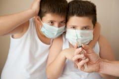 两吓唬了看起来医疗的面具的男孩手头与注射器 库存图片
