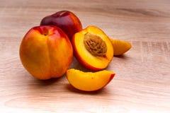 两和在木背景的半油桃 免版税库存照片